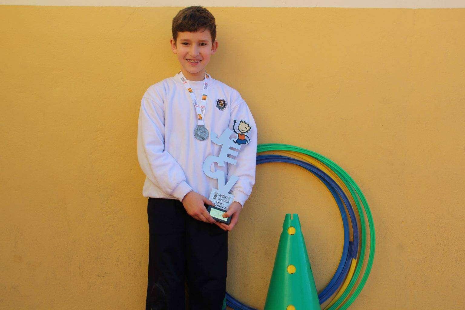 Niño con la copa de oro de la categoría benjamín