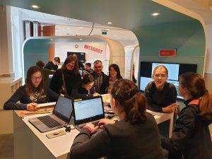 Alumnos y profesores reunidos alrededor de una mesa con ordenadores